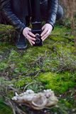 Photographer. Is taking photo of an animal skull on green moss Stock Photos