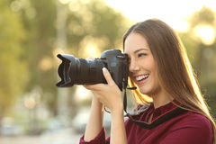 Photographer photographing with a digital camera. Outdoors at sunset with a warm light Royalty Free Stock Images