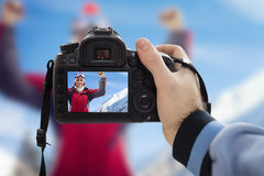 Photographer photographing happy woman on snowy winter day Stock Photos
