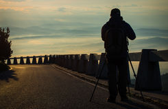 Photographer photographing landscapes. Photographer photographing landscapes morning in hill Royalty Free Stock Photo