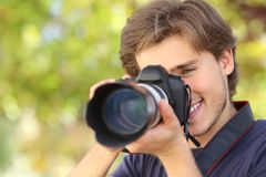 Photographer photographing and learning with a dslr digital camera. With a green background Royalty Free Stock Photos