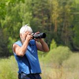 Photographer photographing in nature. Old handsome gray-haired man photographer photographing in nature Royalty Free Stock Images