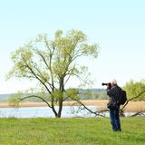 Photographer photographing in nature. Old handsome gray-haired man photographer photographing in nature Stock Photo