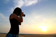 Photographer Photographing at Sunrise. Travel photographer photographing at sunrise Royalty Free Stock Photography