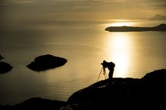 Photographer photographing the sunrise at sea. With an orange reflection on the water. The photographer crouching down looking at the camera on a tripod Royalty Free Stock Images