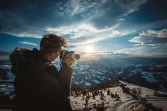 Photographer photographing sunset. Over beautiful winter landscape,back light Stock Photo