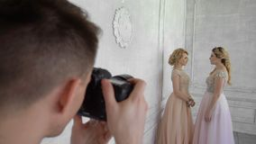 A photographer is photographing two girls on a white wall background. The photographer shoots the woman of blondes in long pink and purple dresses stock video