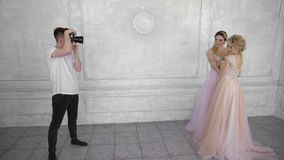 A photographer is photographing two girls on a white wall background. The photographer shoots the woman of blondes in long pink and purple dresses stock footage