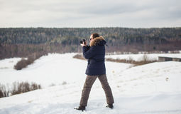 Photographer photographing winter forest panorama in hilly plain. Stock Images
