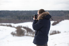 Photographer photographing winter forest panorama in hilly plain. Stock Photos