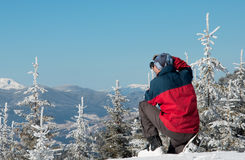 Photographer photographing winter panorama in high mountains. Photographer photographing winter panorama high mountains snow-covered fir-covered Stock Photography