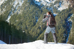 Photographer photographing winter panorama in  mountains Stock Photo