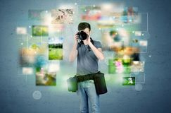 Photographer with pictures from the past. A young amateur photographer with professional camera equipment taking picture in front of blue wall full of faded Royalty Free Stock Photo