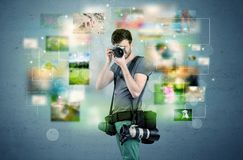 Photographer with pictures from the past. A young amateur photographer with professional camera equipment taking picture in front of blue wall full of faded Royalty Free Stock Photography