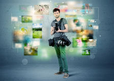 Photographer with pictures from the past. A young amateur photographer with professional camera equipment taking picture in front of blue wall full of faded Stock Photography
