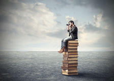 Photographer on a pile of books Royalty Free Stock Photos
