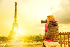 Eiffel Tower woman photographer. Photographer on Place du Trocadero of Tour Eiffel at sunset. Traveler woman in Paris, France, Europe. Eiffel Tower on blurred stock photos