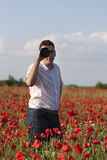 Photographer. A photographer in a poppy field Stock Photo