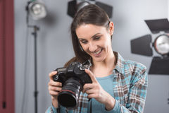 Photographer posing in a professional studio. Young female photographer posing in her professional studio, holding a digital camera with lighting equipment on royalty free stock image