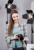 Photographer posing in a professional studio. Young female photographer posing in her professional studio, holding a digital camera with lighting equipment on stock photography