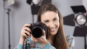 Photographer posing in a professional studio. Young female photographer posing in her professional studio, holding a digital camera with lighting equipment on stock photos