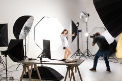 Photographer and pretty model working in modern lighting studio stock image