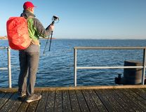 Photographer with red backpack on  wooden pier above sea Royalty Free Stock Image