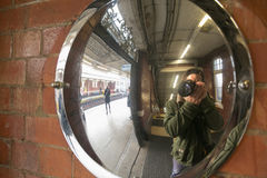 Photographer reflected on a mirror. Caption of selfportrait taken at London Tube Stock Photo