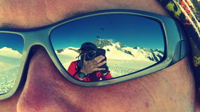 Photographer reflected on sunglasses while climbing Mönch mountain in the Alps, Switzerland.  Stock Photography