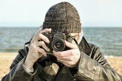 Photographer with retro photo camera on sea beach look at camera Royalty Free Stock Photos