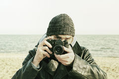 Photographer with retro photo camera on sea beach look at camera Stock Images