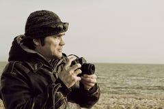 Photographer with retro photo camera on sea beach. Royalty Free Stock Image