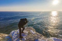 Photographer on the rocks taking landscape pictures. Photographer on the rocks taking beautiful landscape pictures Stock Photos