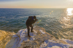 Photographer on the rocks taking landscape pictures Stock Images