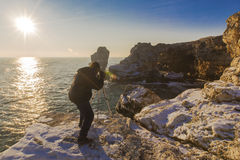 Photographer on the rocks taking landscape pictures Stock Photo