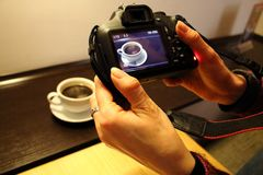 Photographer`s hands holding camera close up with reflection of white coffee cup during shooting photo. stock photography