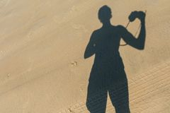 Photographer`s shadow on the sand. Yound man doing the photo of his shadow on the sand. Photographer`s shadow on the sand. Yound man doing the photo of his Stock Photo