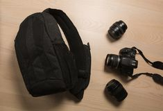 Photographer`s small backpack with digital slr camera and replac. Eable lenses on a wooden background Stock Photo