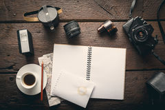 Photographer`s workplace. Empty notepad on the table full of photographic equipment: camera, lens, flash Royalty Free Stock Photography