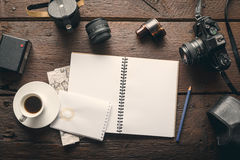 Photographer`s workplace. Empty notepad on the table full of photographic equipment: camera, lens, flash Royalty Free Stock Images