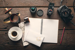 Photographer`s workplace. Empty notepad on the table full of photographic equipment: camera, lens, flash Royalty Free Stock Photo