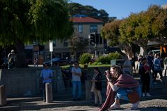 The photographer in the sun, Sausalito California on a Sunday afternoon. Street scene. A woman is crouched to take a picture in Sausalito California. She may be royalty free stock photos