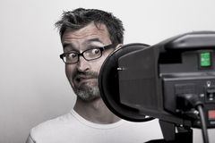 Photographer sceptically looks into a studio strobe. Photographer irritated looks into a studio strobe royalty free stock images