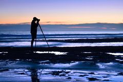 Photographer at the sea in the dusk Royalty Free Stock Images