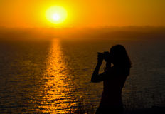 Photographer by the sea. Female photographer silhouette at dusk Stock Photography
