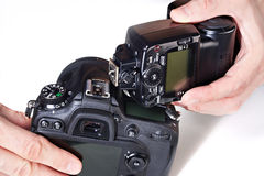 Photographer set external flash on digital SLR camera Royalty Free Stock Photo