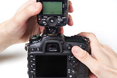 Photographer set external flash on digital SLR camera Royalty Free Stock Image