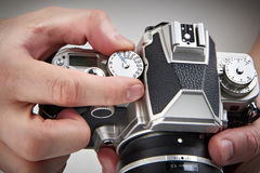 Photographer setting shutter control dial on retro SLR camera Stock Images