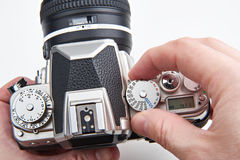 Photographer setting shutter control dial on retro SLR camera Royalty Free Stock Image