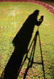 Photographer Shadow. Shadow on the photographer in the grass with camera and tripod Royalty Free Stock Images